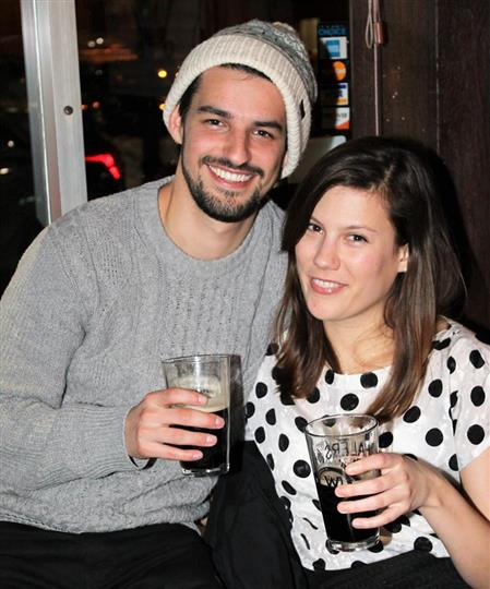 male and female in picture, both are smiling and holding glasses of beer