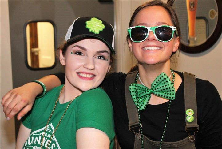 two females smiling in photo, one is wearing a hat, other female has on sunglasses and large bow tie
