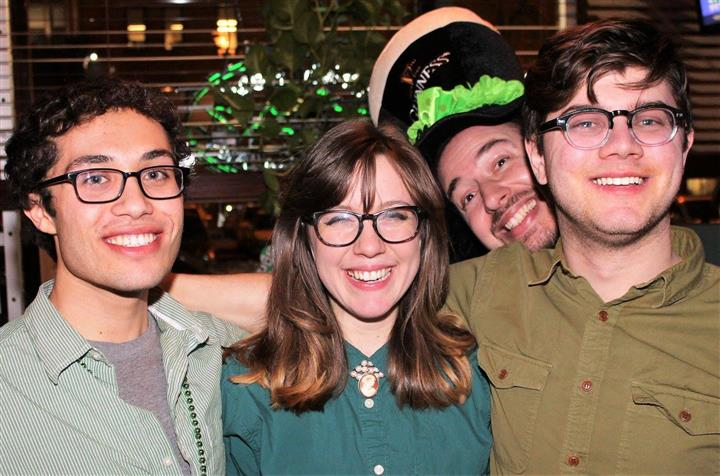 four people smiling in photo, one is wearing a hat