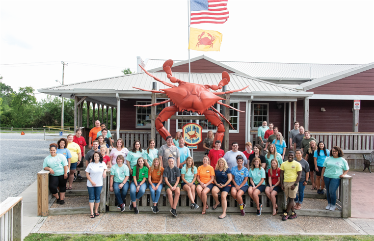 Old Mill Crab House Staff posing for a picture in front of the business