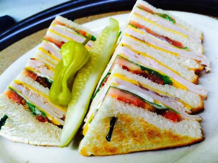 club sandwich with a pickle and a pepper