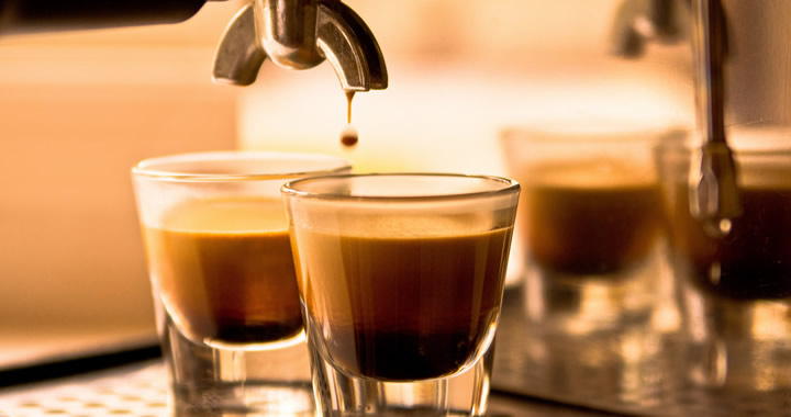 Coffe shot glasses filled with fresh coffee dripping from the espresso machine