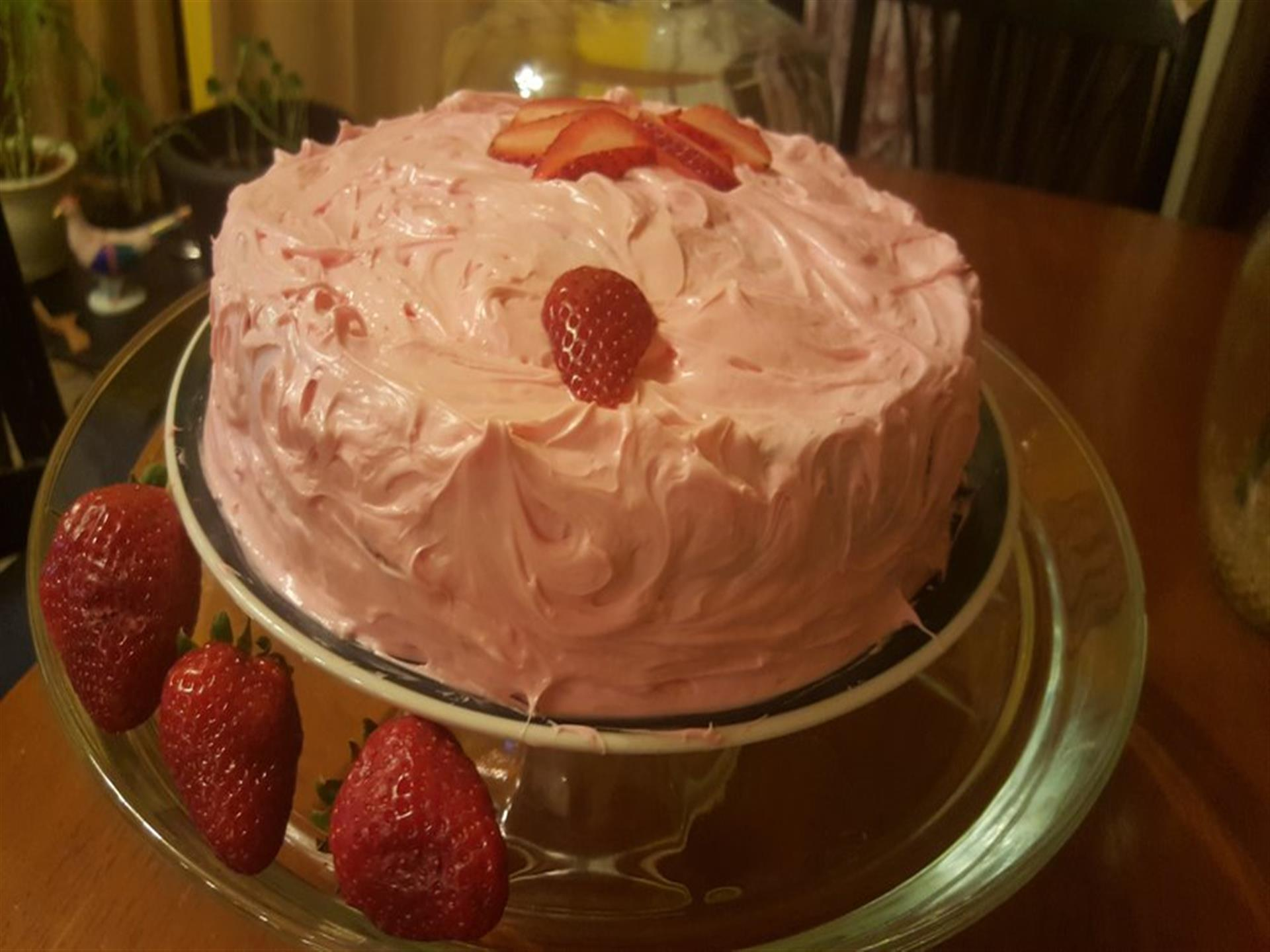 Strawberry frosted cake topped and garnished with strawberries on dish