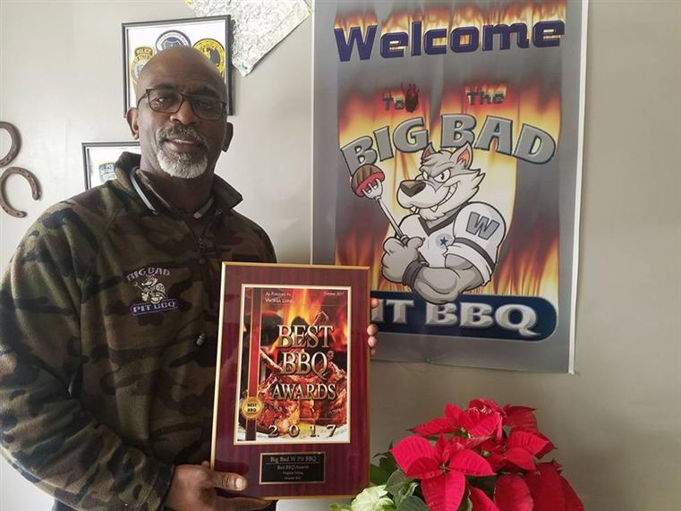 Man holding Best BBQ Award 2017 in front of Welcome to the Big Bad Pit BBQ on wall.
