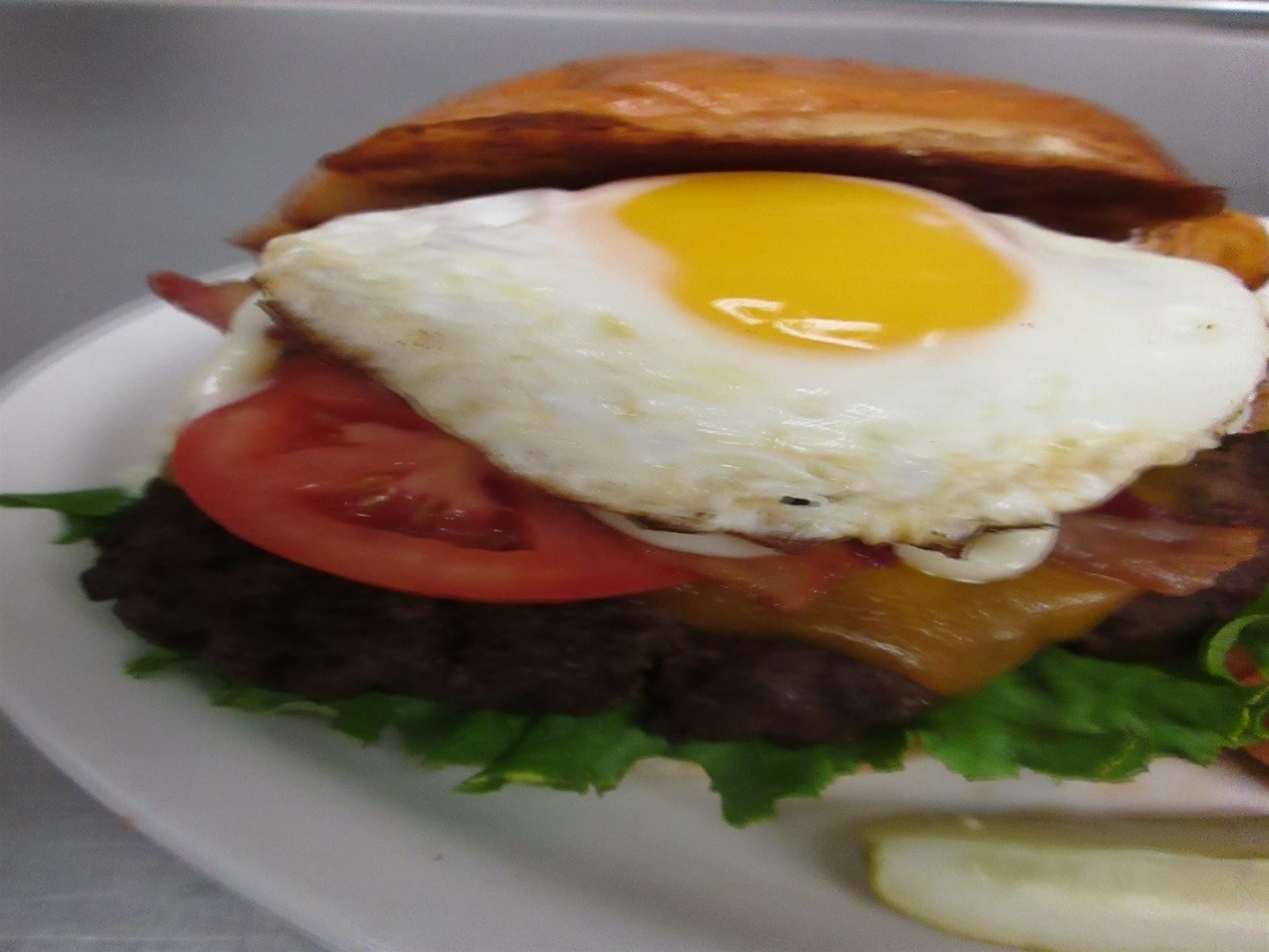 early riser burger. Cheddar Cheese, crispy bacon, lettuce,tomato, mayonnaise, topped with a fried egg.