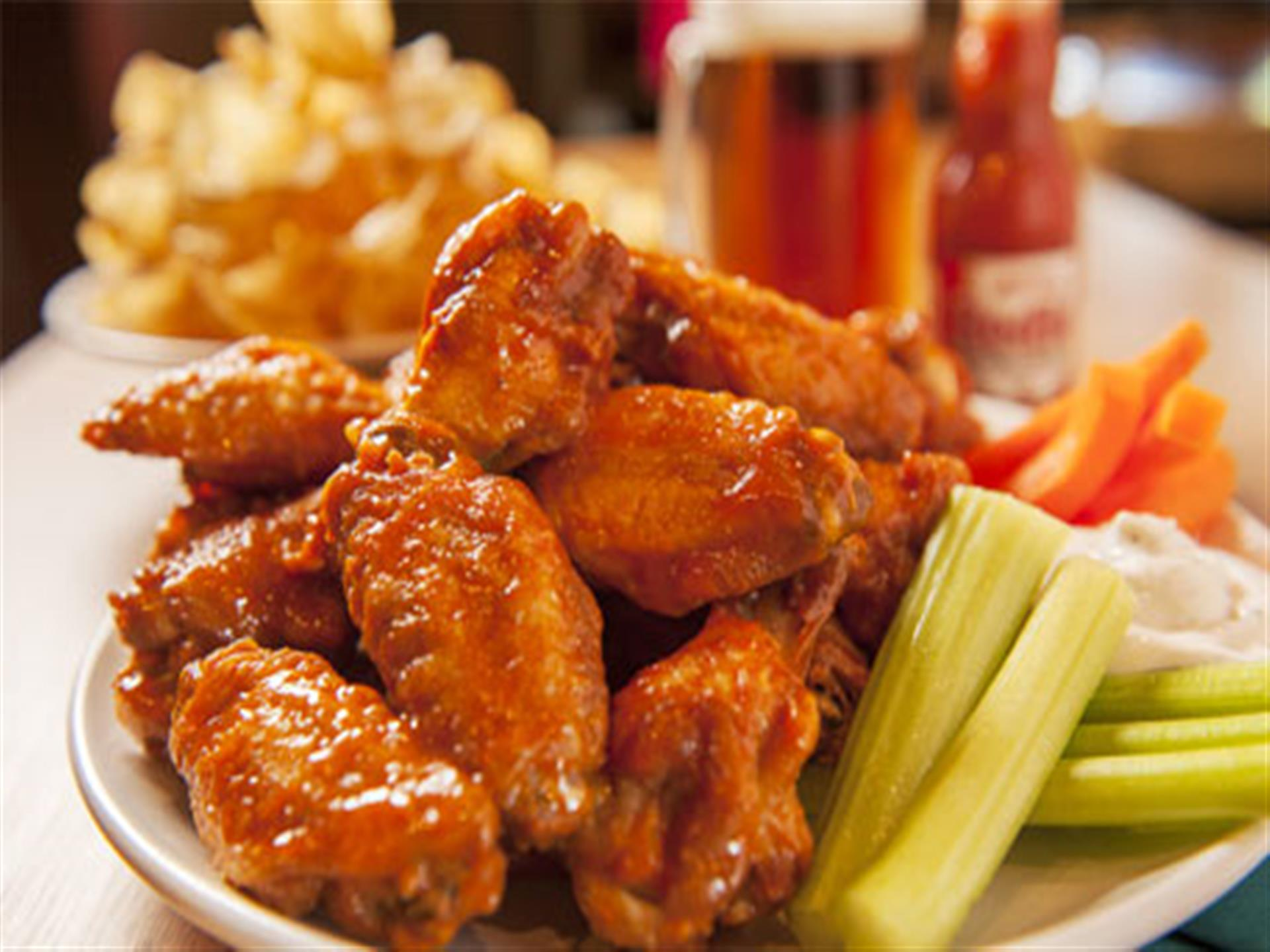 dish of hot wings with celery, carrots and hot sauce and beer in background.