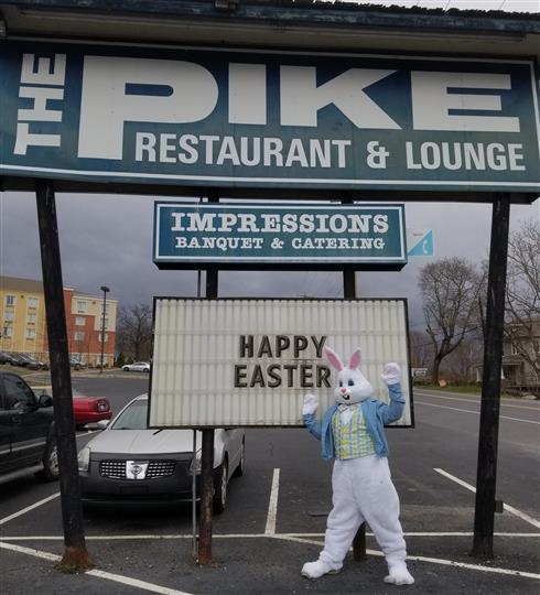 Easter bunny standing next to sign