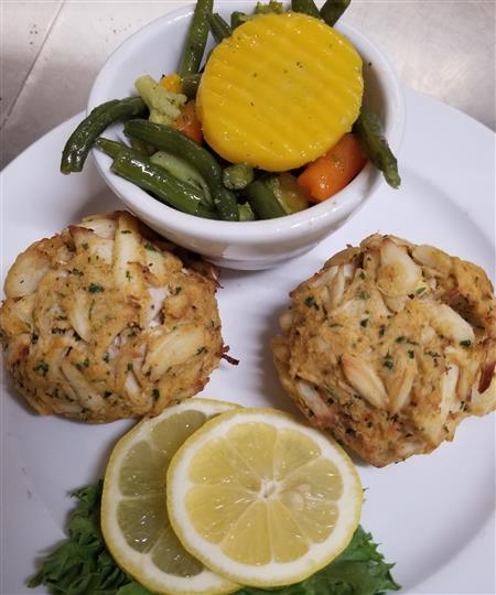Fish with a side of lemon and a bowl of vegetables