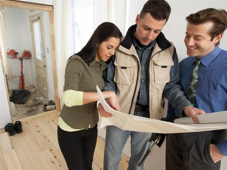 three people looking at construction plans