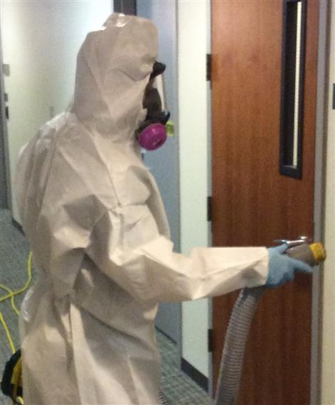 employee cleaning wearing a hazmat suit