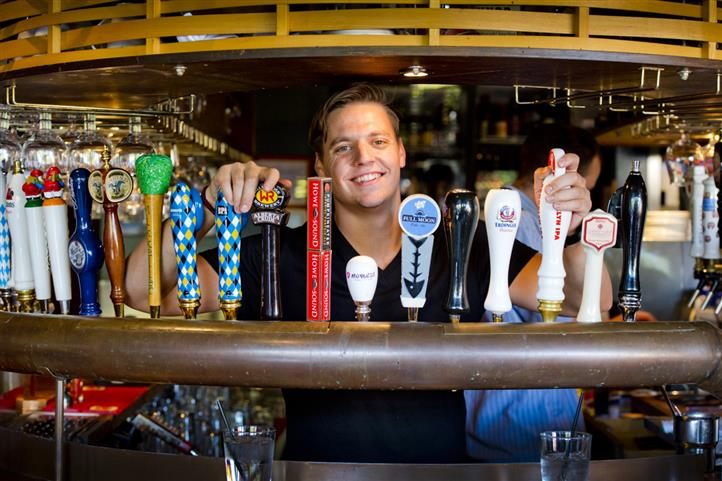 bartender behind beer taps smiling at the camera