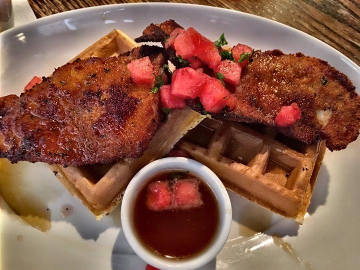 fried chicken on waffles with tomatoes and syrup