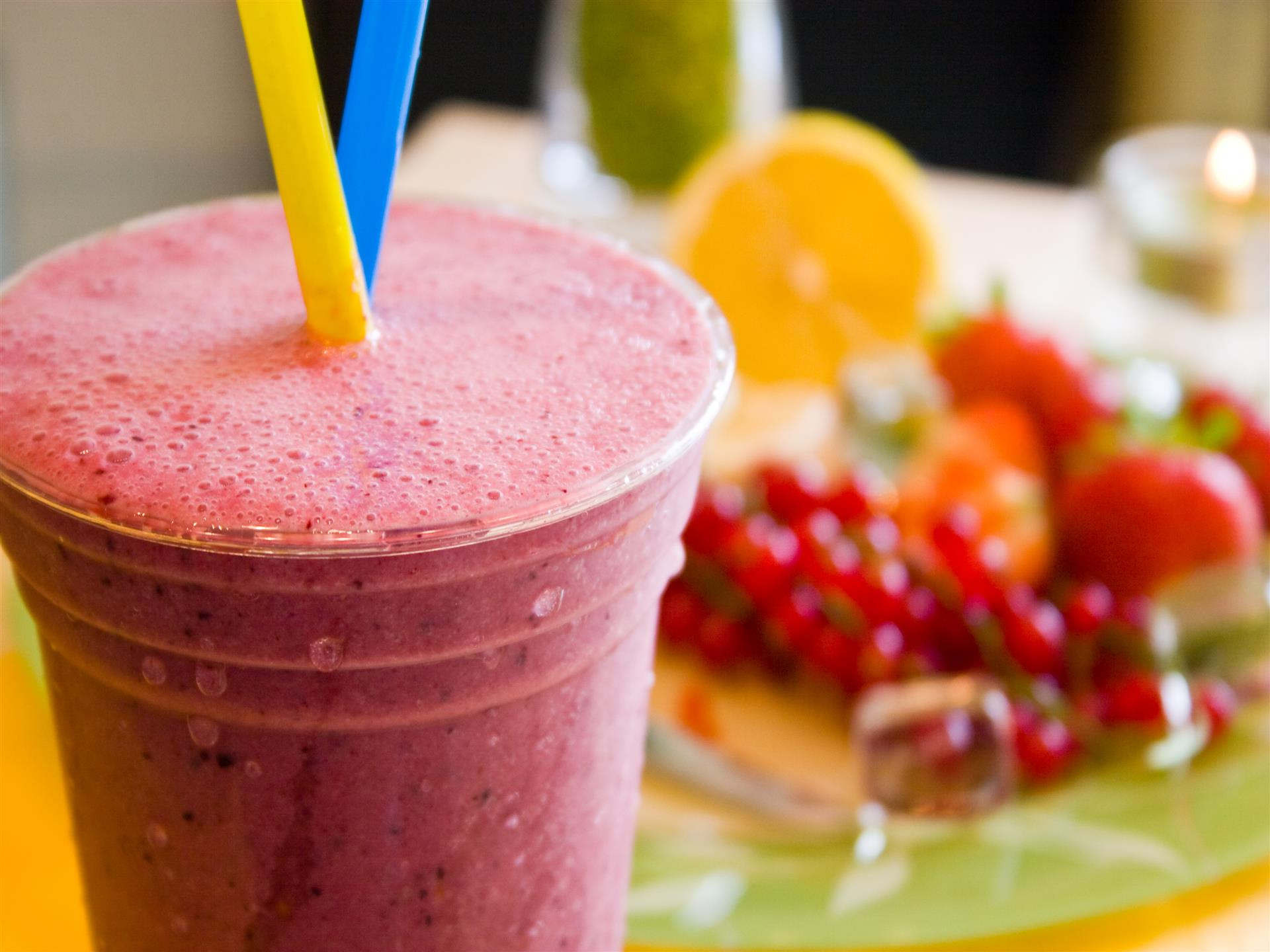 smoothie with two straws and assorted fruit in background