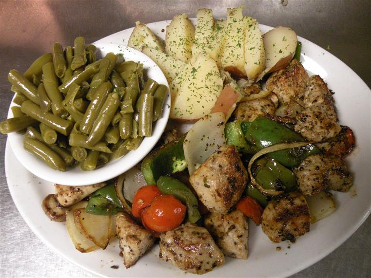 Marinated chicken with potatoes, onions, peppers and side of green beans.