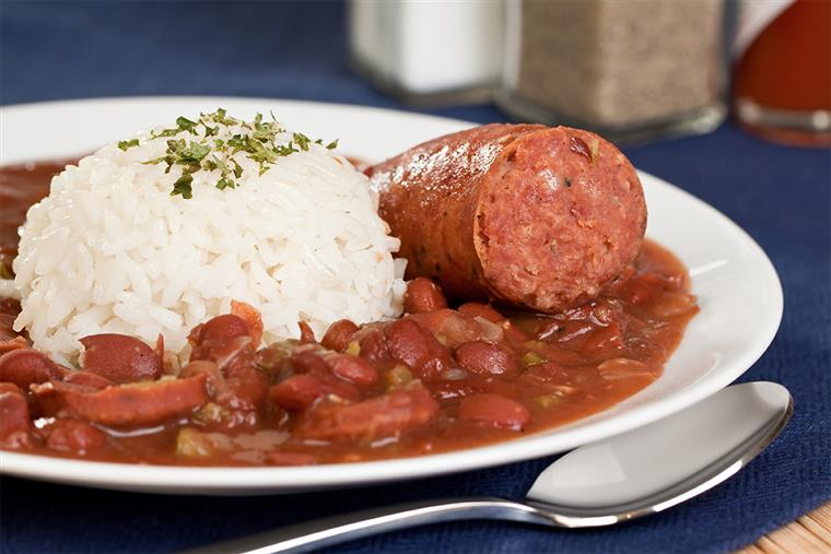 sausage with rice and beans on a white plate with a spoon on  a blue tablecloth