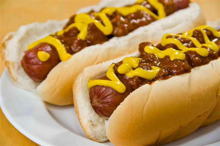Image of two hot dogs on buns topped with mustard and chili
