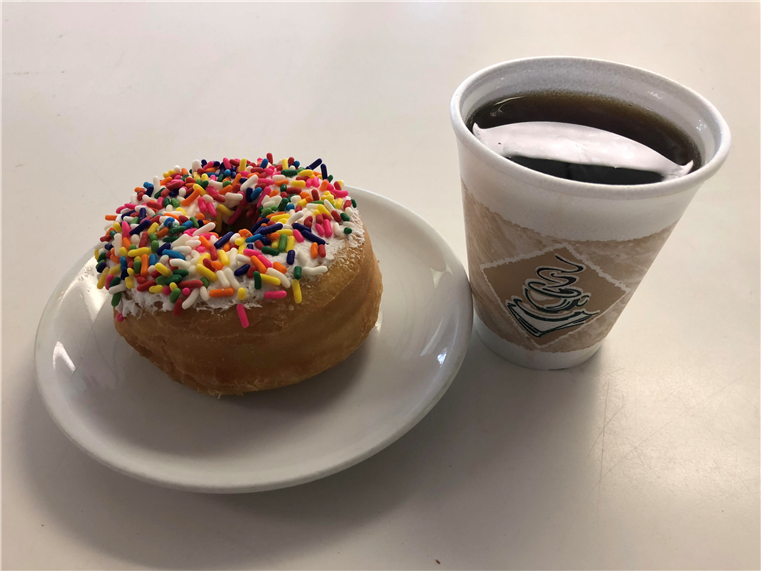 doughnut topped with sprinkles and a cup of coffee