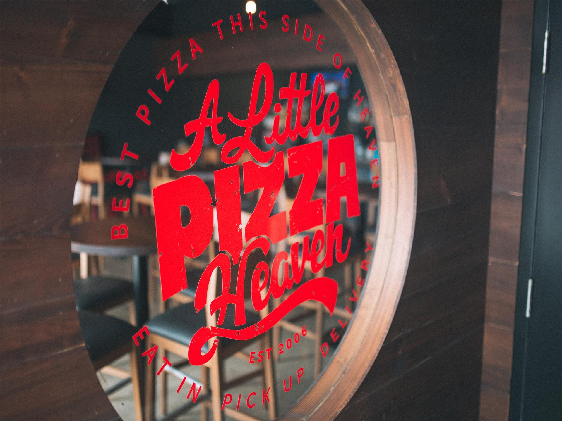 A litte pizza heaven decal sign in restaurant window
