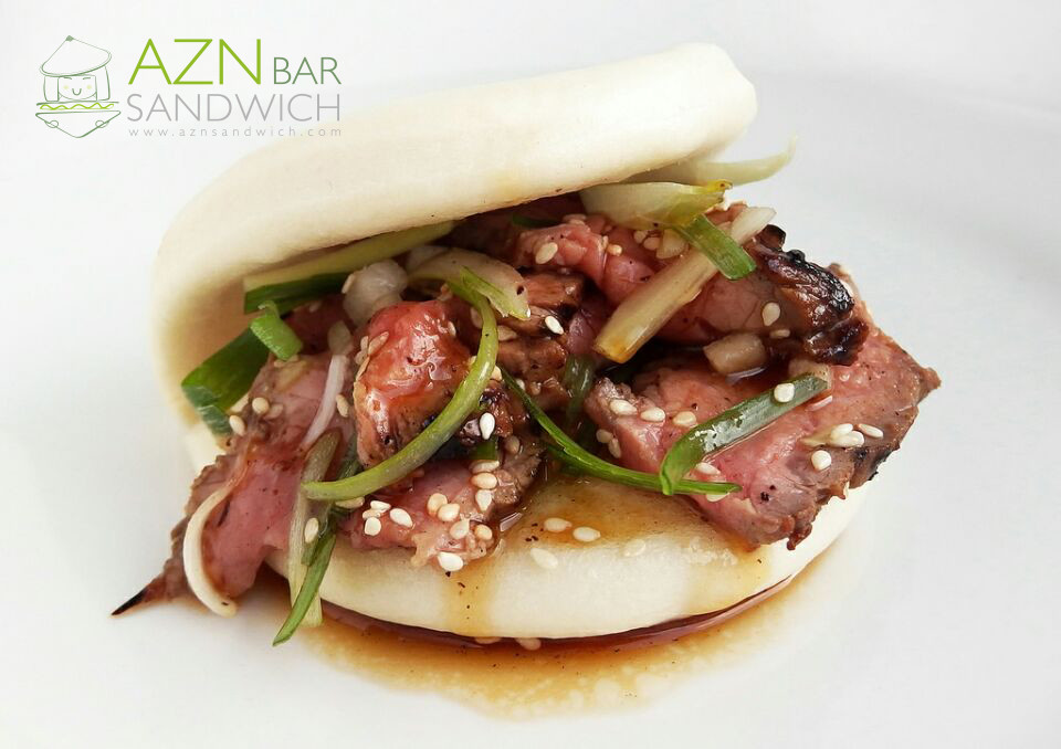 menu item on a bao bun with meat and onions