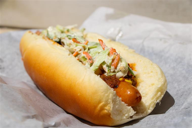 hot dog topped with chili and coleslaw