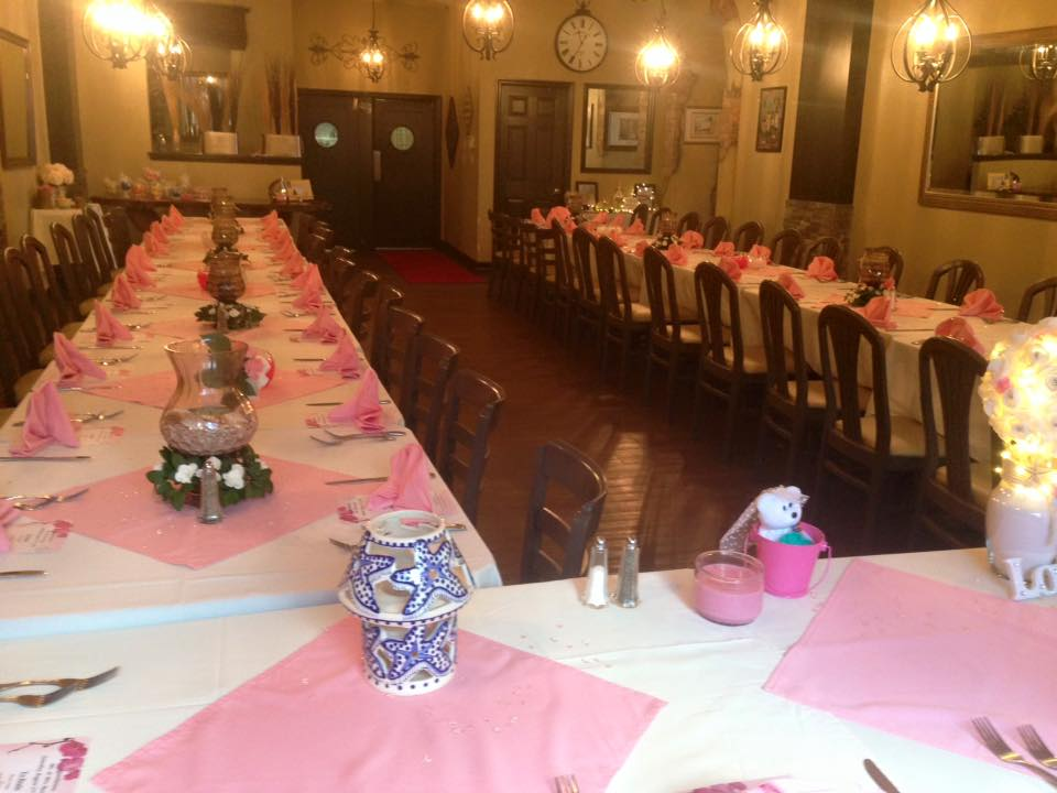 a long party table with white tablecloths, napkins, meuns, nad centerpieces