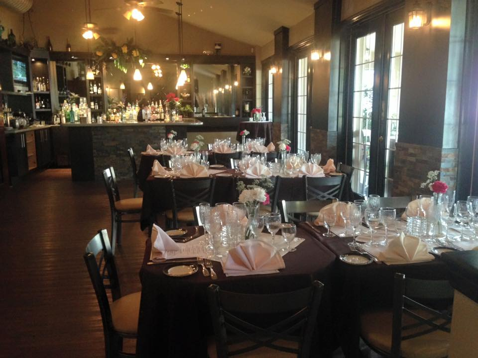 multiple tables and chairs with napkins, glasses, and flower centerpieces