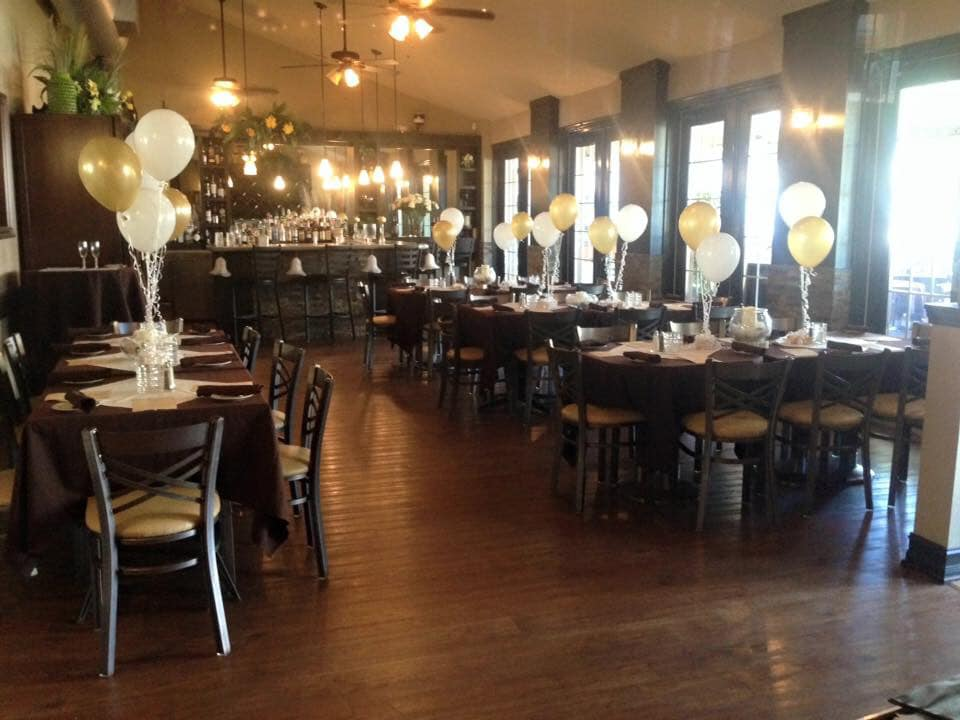 multiple tables and chairs with white tablecloths, and ballooon centerpieces