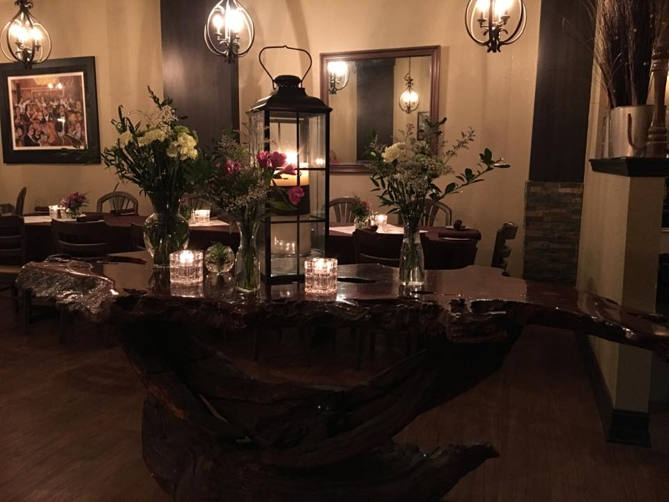 a wooden table with candles, flower vases, and a lantern on it
