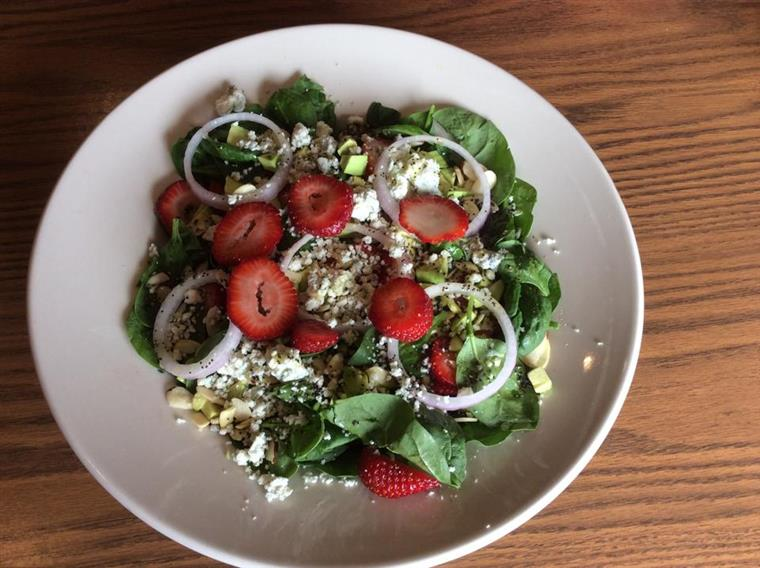salad with greens, blue cheese crumbles, red onion, and strawberries