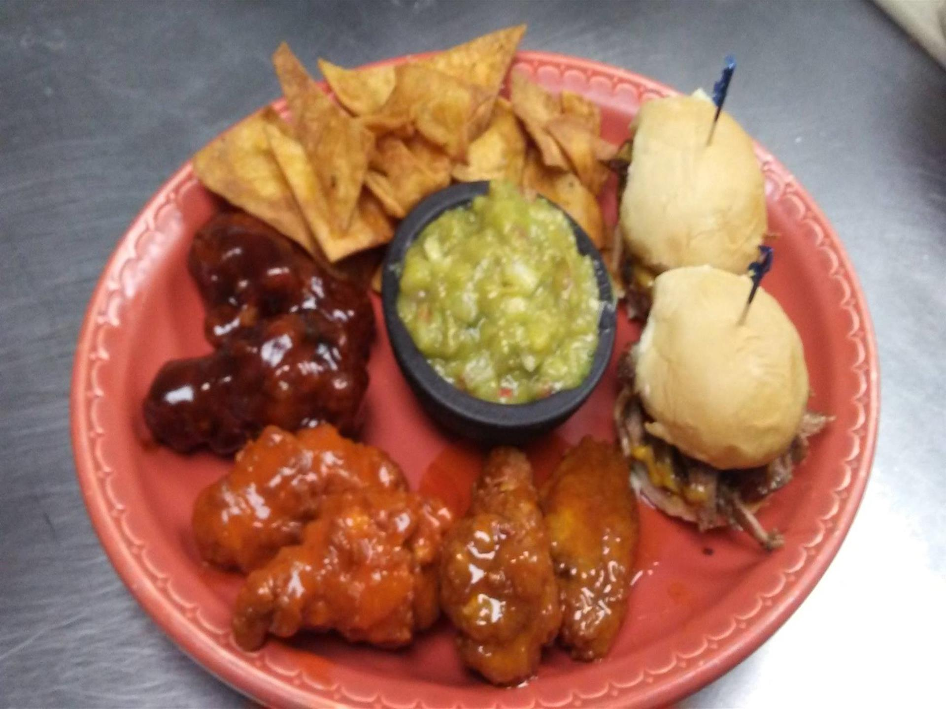 Assortment of appetizers on red plate. Wontons, glazed chicken wings, two sliders and guacamole dip.