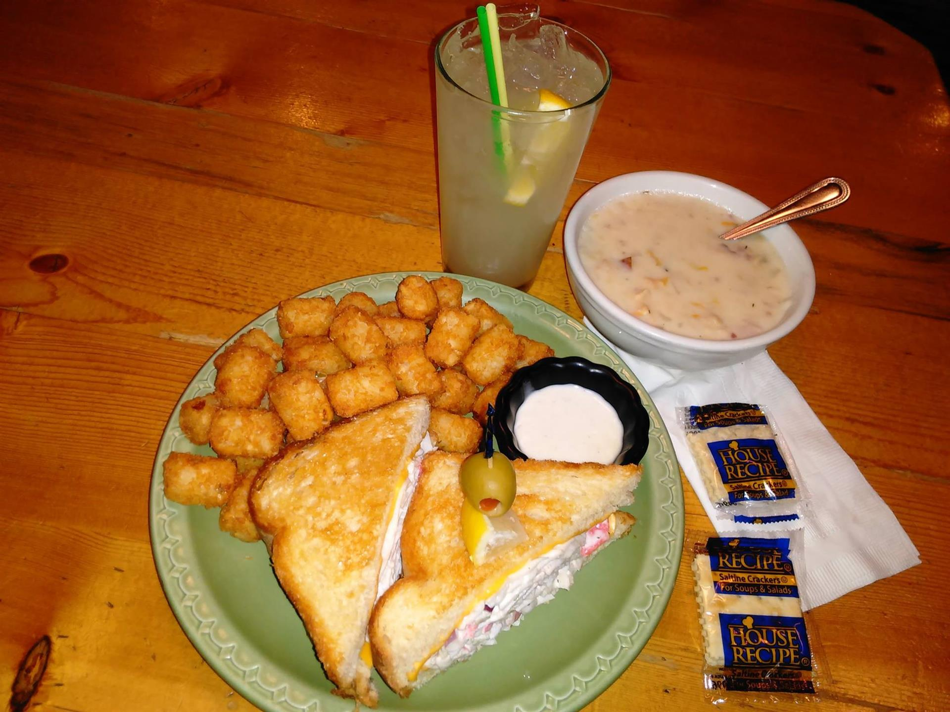 Sandwich with tater tots and cup of soup, water with lemon on wood table