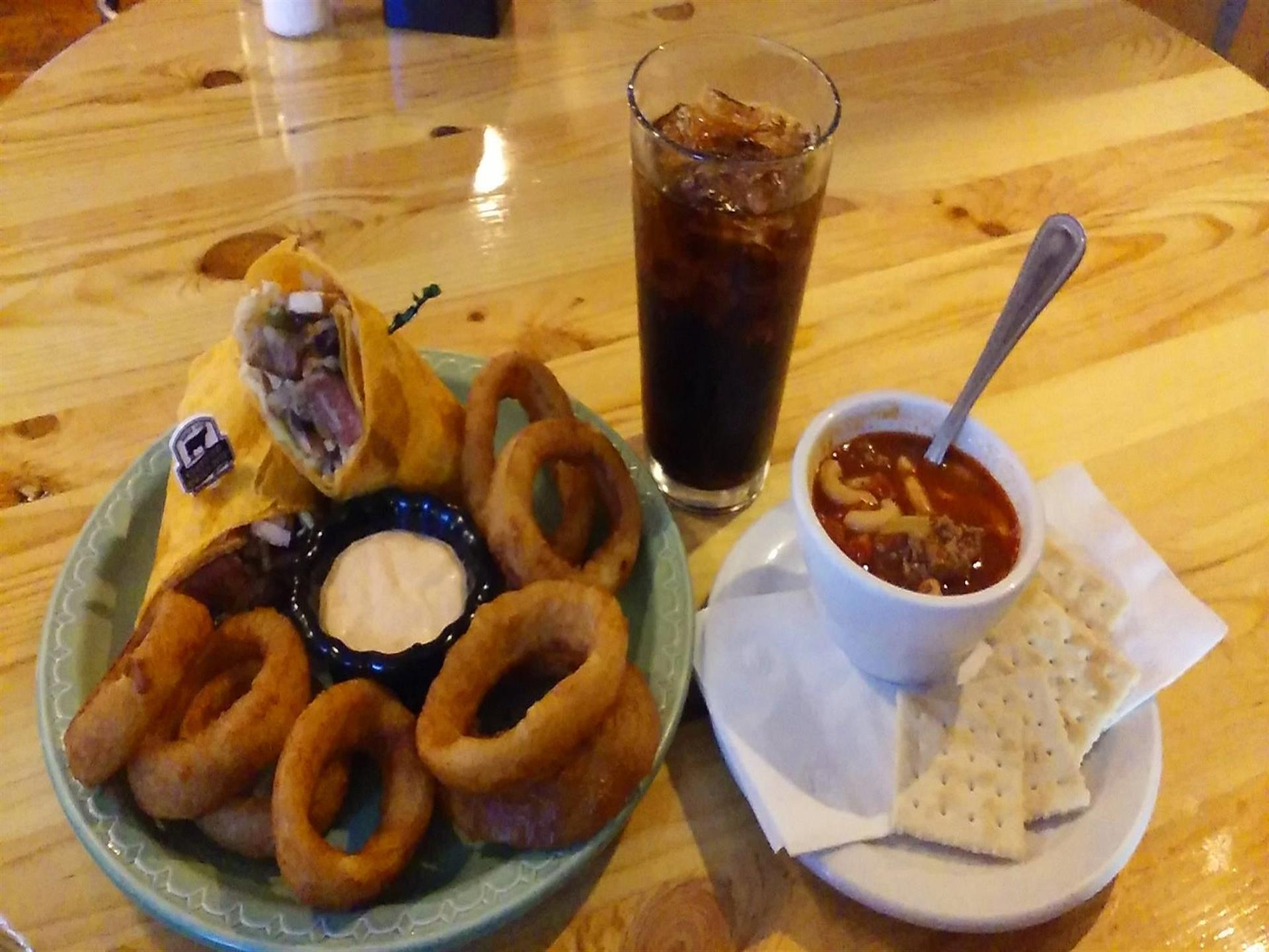 Onion rings and wraps on plate next to cup of soup with crackers and glass of soda on light-colored wood table.