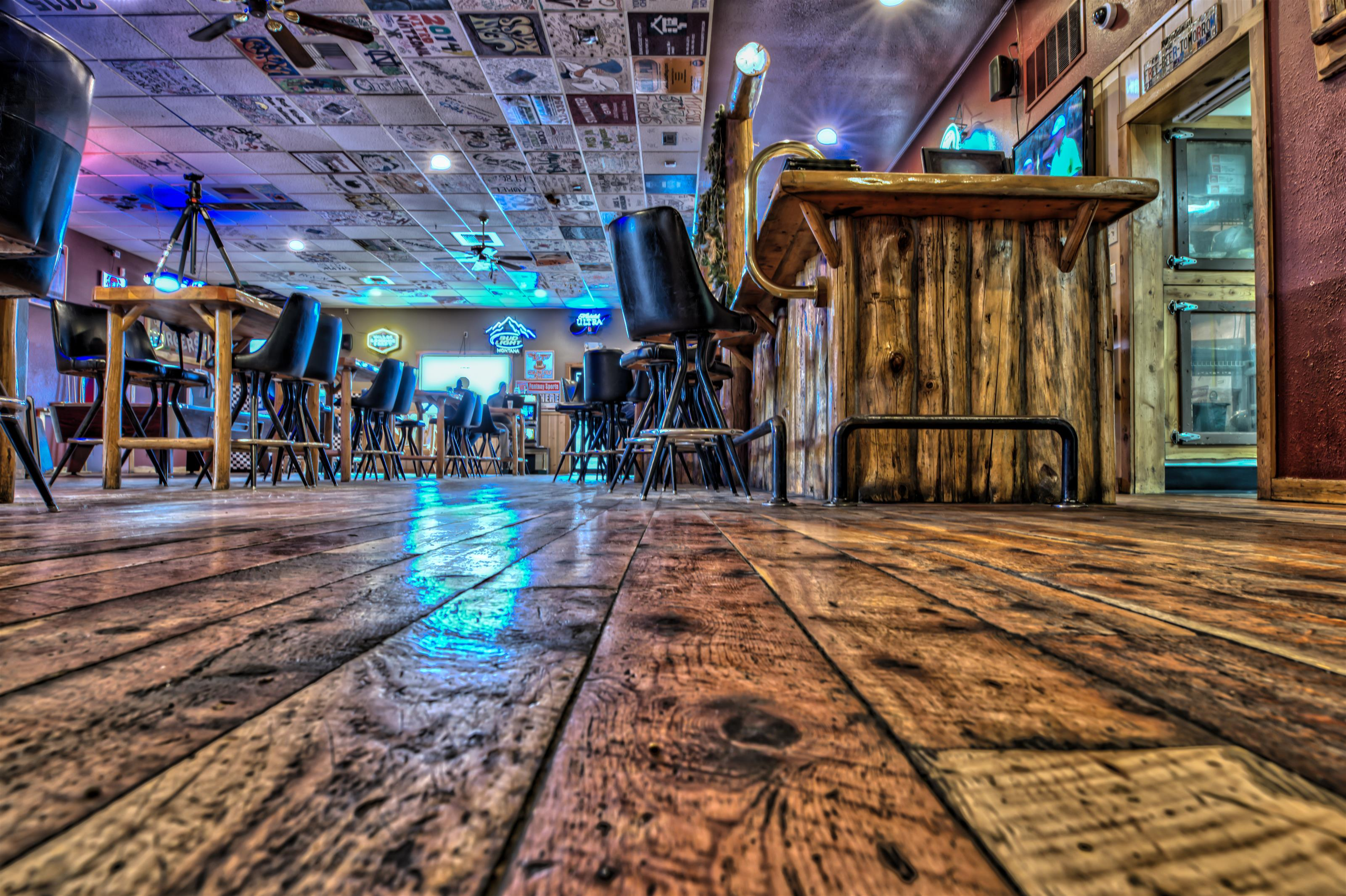 view from floor of inside of restaurant with wooden bar and bar stools