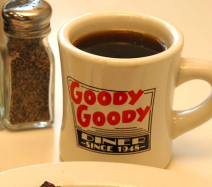 Mug of coffee with the Goody Goody diner logo and a side pepper shaker
