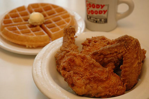 fried chicken, a side waffle with butter and a mug with the Goody Goody diner logo on it