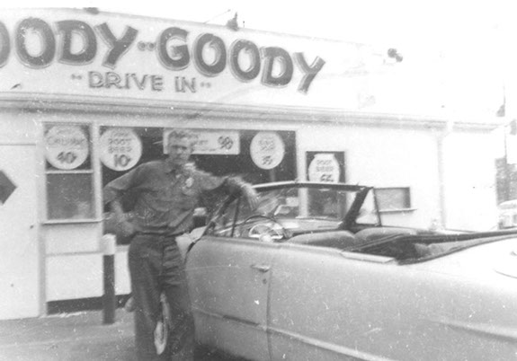 vintage photo of a man outside the business leaning against his car