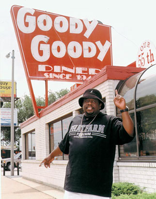 man standing outside of the business pointing up to the sign