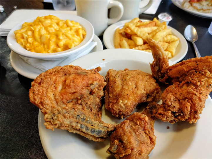 4 pieces of fried chicken with a side of french fries and macaroni and cheese