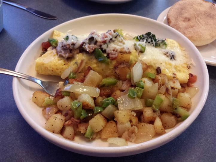 omelette with a variety of ingredients and a side of diced potatoes