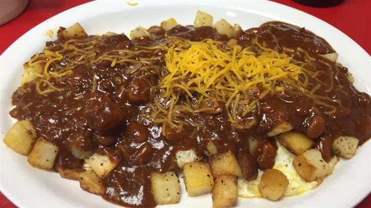 bowl of beans in a sauce with potatoes and topped with cheddar cheese