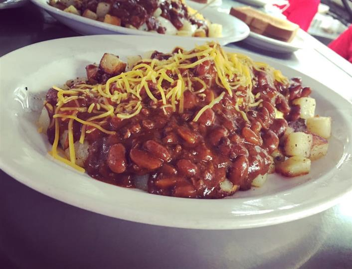 bowl of beans in a sauce topped with cheese
