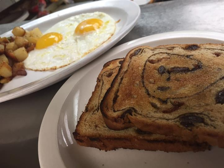 two pieces of cinnamon raisin toast with two eggs sunny side up in the background