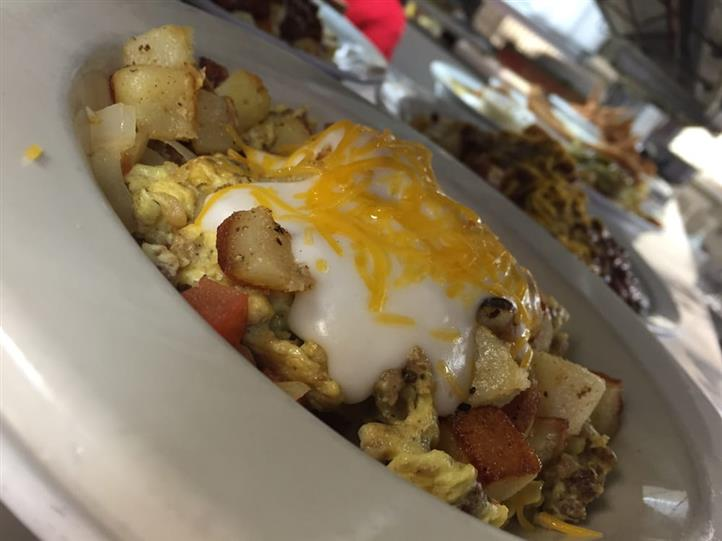 bowl of scrambled eggs with a variety of ingredients and topped with melted cheese