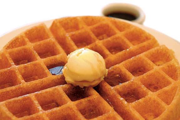 A waffle topped with maple syrup and a scoop of vanilla ice cream