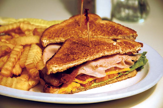 A clab sandwich served with French fries