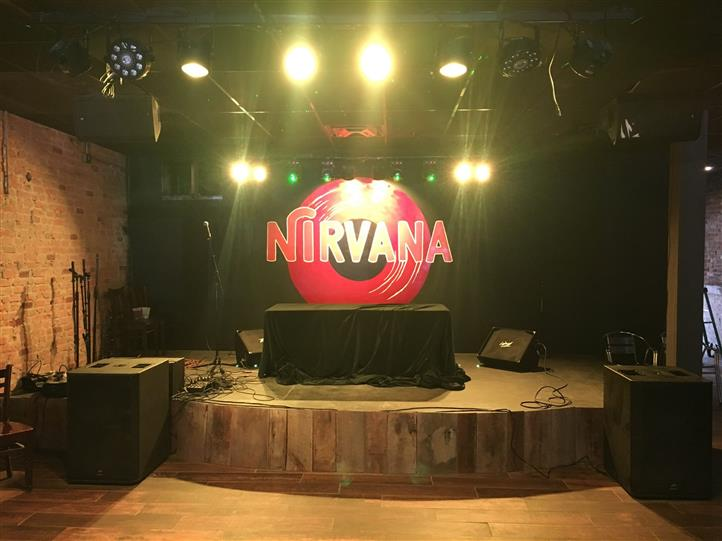 stage for a band with speakers and a nirvana sign