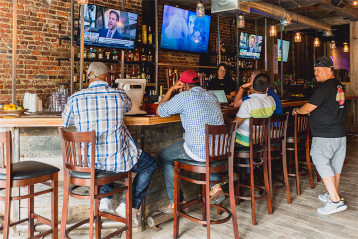 people sitting at the bar with televisions hanging on the wall