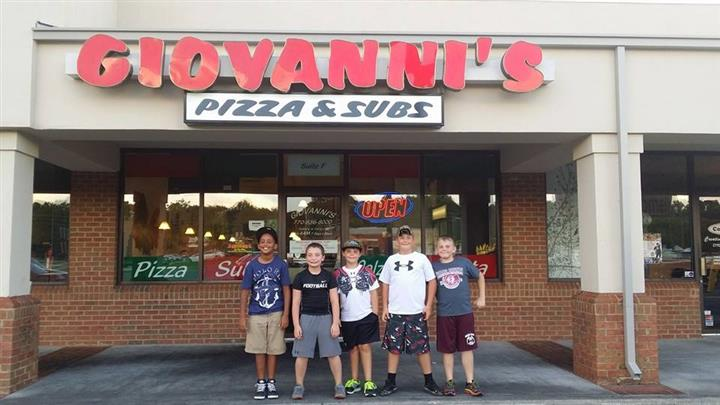 young boys standing in front of restaurant