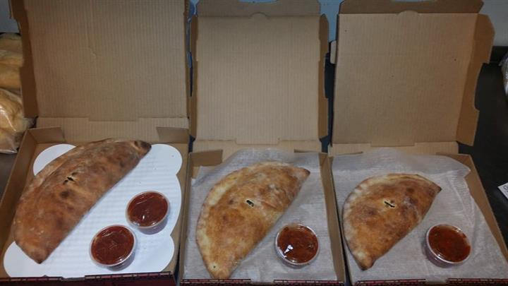 calzones in boxes with dipping sauce