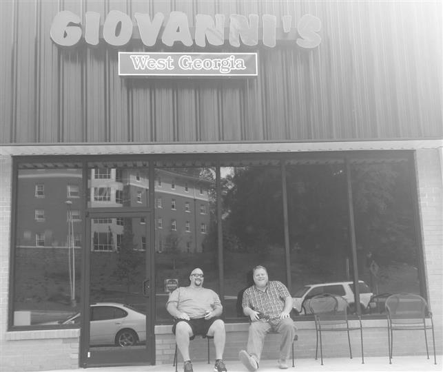 black and white photo of two men sitting in front of restaurant